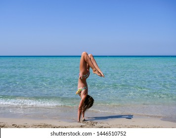 Slim and athletic girl doing yoga pose, calisthenics, fitness training on a wonderful beach with crystal clear water -vacation-fitness-wellness