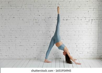 Slim athletic girl on a white brick background in a standing yoga pose, Urdhva Prasarita Eka Padasana, stretching exercise