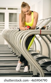 Slim athletic girl running on a treadmill in a gym. Active lifestyle. Healthcare, body care.