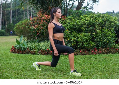 Slim athletic woman working out in park doing knee-bounce exercise or lunges.