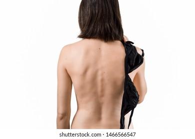 Slim attractive abrunette woman holding black bra in hand. Breast cancer concept.
