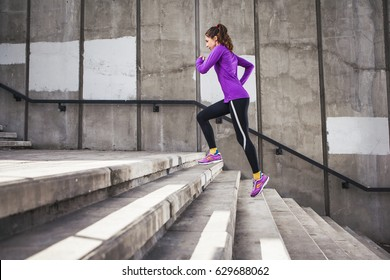 Slim attractive sports women running against a concrete wall