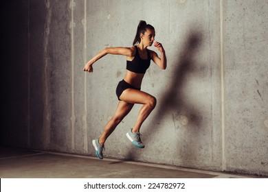 Slim attractive sportswoman running  against a concrete background