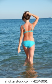 slim back of young woman standing in water against blue sea