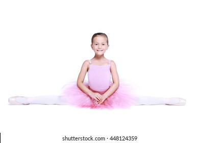 Slim ballet dancer girl in pink pointe and tutu isolated on white, little balerina is sitting in the splits facing directly front in cross twine and smiling. Education lessons in Classic dance school