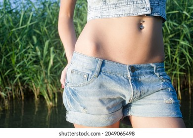 Slim bare belly of young lady in denim sharts outside in the nature in front of the reeds
