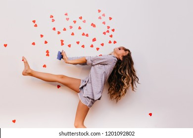 Slim barefooted lady in sleepwear having fun during morning tea. Carefree white girl fooling around while posing with cup of coffee.