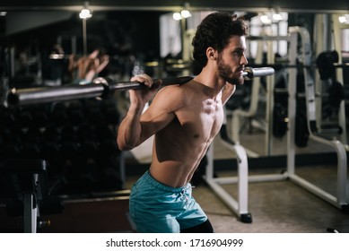 Slim bearded young man with muscular wiry naked torso performing barbell squats during sport workout training in modern dark gym. Concept of healthy lifestyle.