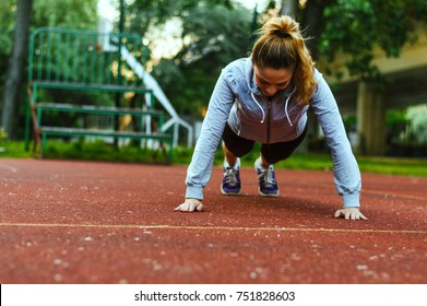 Slim beautiful athletic woman doing pushup exercise.