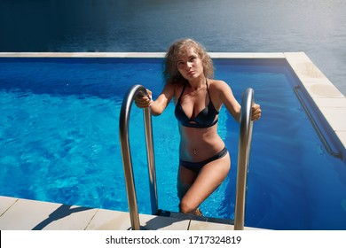 Slim, beautiful girl coming out of pool, holding stairs of swimming pool. Seductive model in black swimsuit with curly blonde hair posing at pool, looking at camera. Concept of pool outdoors.
