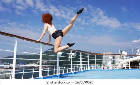 Slim beautiful girl dancer on observation deck cruise ship jumping dance elements. beautiful lines of red-haired curly-haired European girl on blue podium, background of an Asian city. modern dance
