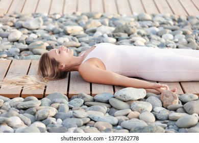 slim beautiful gorgeous blonde female athlete in a white suit resting lying on her back on a wooden platform among the stony beach in a warm summer evening. Concept of nirvana and relaxation