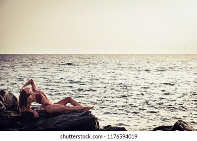 slim and beautiful perfect body young brunette girl taking a sunbath on the rocks lay down near the ocean, paradise resort concept and enjoying summer vacation. horizon and sky in background