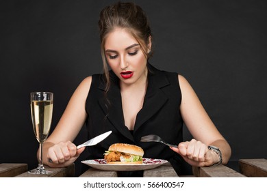 Slim beautiful woman eating a hamburger. Fashionable young woman holding knife and fork and going to eat burger