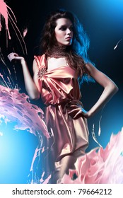slim beautiful woman in pink dress and paint splash