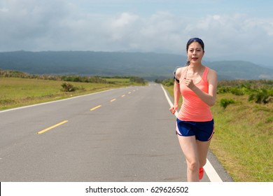 slim beautiful woman running on a clean road listen to music training the body efforts to maintain body with spectacular background.