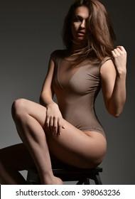 Slim beautiful woman sitting on a chair in sexy underwear on dark background