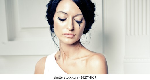 Slim beautiful woman wearing luxurious wedding dress. Bride with beautiful make up and hairstyle is posing against the white wall