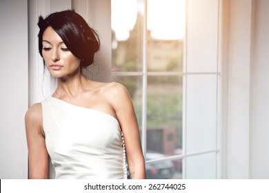 Slim beautiful woman wearing luxurious wedding dress. Bride with beautiful make up and hairstyle is posing against the window