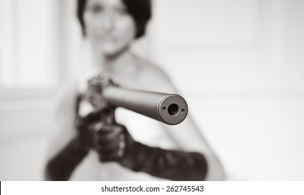 Slim beautiful woman wearing luxurious wedding dress. Bride with gun is posing against the white wall