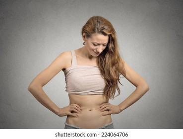 slim beautiful young girl looks at her abdomen concerned face expression