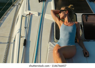 Slim beautiful young woman wearing blue one-piece swimsuit and sunglasses is lying, sunbathing on the deck of the luxury yacht