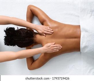 Slim black woman receiving full body massage at modern spa, top view