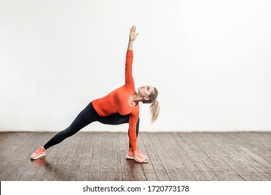 Slim blond woman in tight sportswear practicing yoga, standing in trikonasana triangle pose, training muscles for flexibility. Health care, sports activity and workout at home. indoor studio shot