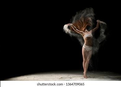 Slim blonde in bandage in dust cloud in the dark