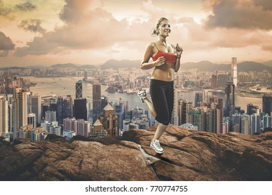 slim blonde girl jogging up to the rocks hill over the metropolis