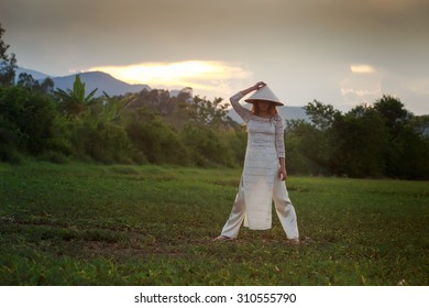 slim blonde girl in Vietnamese national white long dress lifts hat above head on field against sky at sunset
