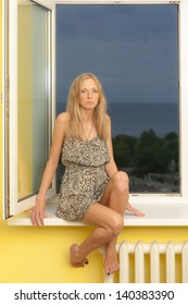 Slim blonde on the windowsill with the sea outside the window