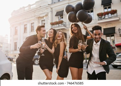 Slim blonde woman with lightly-tanned skin dancing during outdoor photoshot with friends. Black man with african hairstyle waving hand, drinking wine on the street.