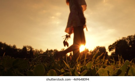 Slim blurred barefoot girl holding her high heel shoes in hand. Orange sunset colors