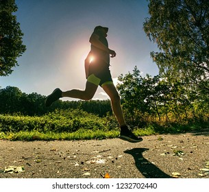 Slim body guy runs on path with fallen leaves. Warm day for outdoor excersising.