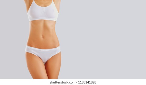 Slim body of a young woman in lingerie.