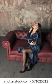 slim brunette in a blue velvet dress