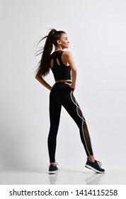 Slim brunette fitness woman runner sprinter before workout exercise in purple sport wear full body on gray background