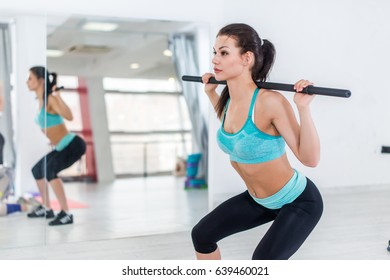 Slim brunette woman doing squats with barbell in fitness hall