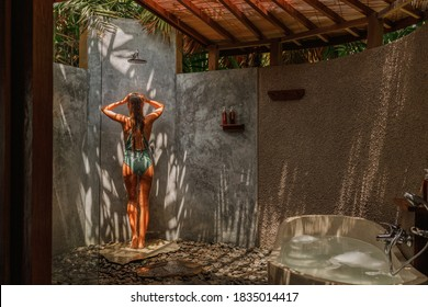 Slim brunette woman taking shower outdoor in tropical garden in Bali, shadow from palms on grey wall