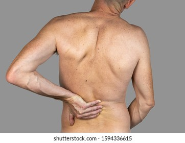 Slim caucasian man with hand on his back feeling pain, isolated on gray background