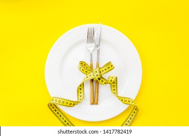 Slim concept with plate, flatware and measuring tape on yellow background top view