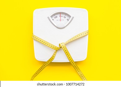 Slim concept. Scale and measuring tape on bright yellow background top view