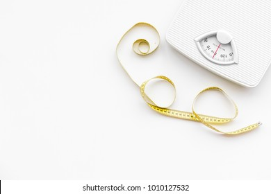 Slim concept. Scale and measuring tape on white background top view space for text