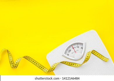 Slim concept with scale and measuring tape on yellow background top view mockup