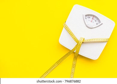 Slim concept. Scale and measuring tape on bright yellow background top view space for text