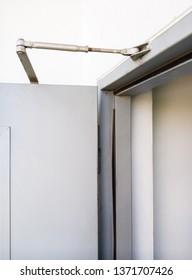 Slim door closer is installing on the metal door of the fire escape, office building.