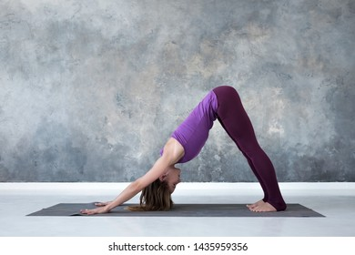 Slim european woman doing yoga exercise downward facing dog pose or adho mukha svanasana. Full length, side view