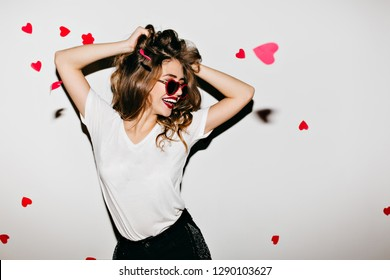 Slim european woman in glamorous sunglasses laughing on white background. Photo of good-looking girl playing with her wavy hair.