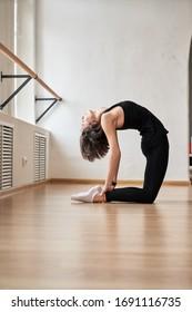 Slim female in black sportswear doing yoga in dance studio
